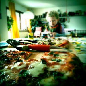 Luftige Pizza und Pizzaschneider vor Kleinkind