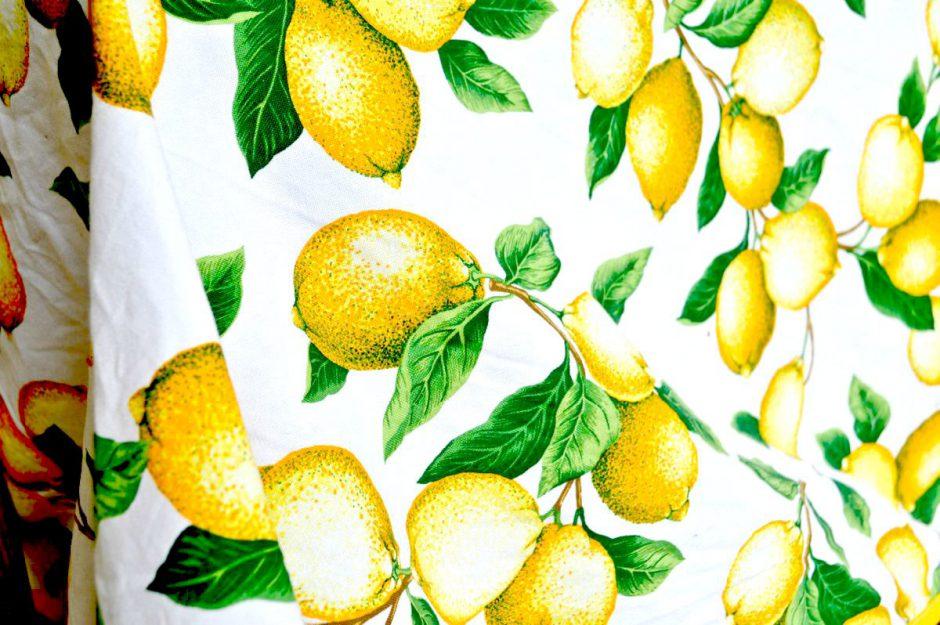 Weiße Tischdecke mit vielen gelben reifen Zitronen